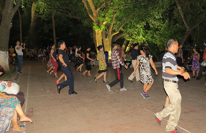 Vietnamitas dançam em torno do lago