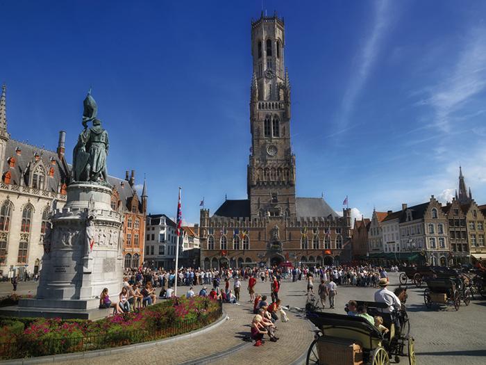 No meio da praça, a estátua do açougueiro Jan Breydel e do tecelão Pieter de Coninck, fervorosos combatentes na luta pela independência de Bruges. Foto do site.