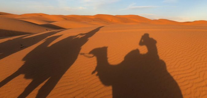 De camelo, pelo deserto do Saara, no Marrocos